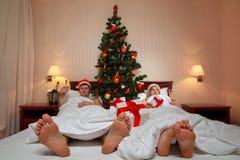 Couples se trouvant sur le bâti avec l'arbre de Noël Images libres de droits