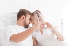 Couples se trouvant sur le lit formant la forme de coeur avec la main Photos stock