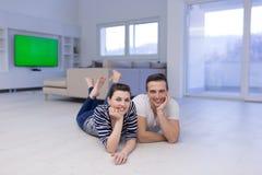 Couples se trouvant sur le plancher à la maison Photos stock