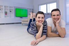 Couples se trouvant sur le plancher à la maison Photographie stock libre de droits