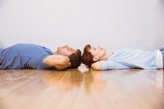 Couples se trouvant sur le plancher Image libre de droits