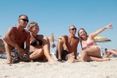 Couples se trouvant sur le sable l'été Image libre de droits