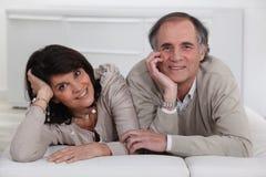 Couples se trouvant sur un futon Photo stock