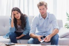 Couples semblant soucieux tout en faisant leurs comptes Photos libres de droits