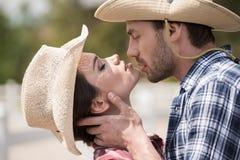 Couples sensuels de style de cowboy embrassant avec des yeux fermés dehors Images libres de droits