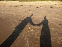 Couples shadow on beach. A shadow of a couple holding hands on the San Padre Island beach with a heart in the sand stock image