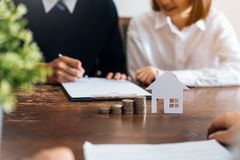Free Couples Signed A Contract To Buy A House From The Broker. Coin To Stack Money And Model Houses Placed On The Table. Royalty Free Stock Image - 149490386