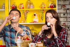 Couples sirotant une boisson de petites tasses au café Photographie stock libre de droits