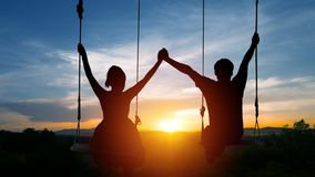 Couples sit on swings and join hands. On the background of the s. Unset Stock Photo