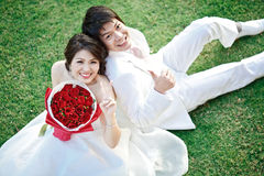 Couples sitting on grass Stock Image