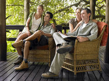 Couples Sitting In Wicker Chairs On Terrace Stock Photo