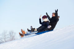 Couples sledging Images stock
