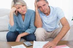 Couples soucieux allant au-dessus des factures regardant l'appareil-photo Image stock