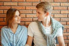 Couples souriant à l'un l'autre sur le fond de mur de briques Photo stock