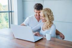 Couples souriant comme ils vérifient leur media social Image libre de droits