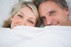 Couples souriant de dessous les couvertures Photos libres de droits