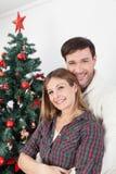 Couples souriant près de l'arbre de chrismas Photos libres de droits