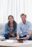 Couples souriant tout en faisant leurs comptes Photographie stock libre de droits