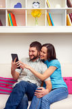 Couples souriants se reposant sur le sofa Photographie stock