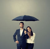 Couples souriants sous le parapluie Image stock
