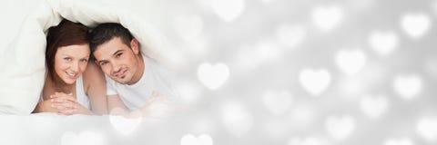 Couples sous la couette avec les coeurs de transition de l'amour de la valentine Photos libres de droits
