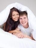 Couples sous la couverture Images stock