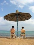 Couples sous le parapluie. mer. Photographie stock