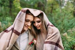 Couples sous le plaid en automne romantique de forêt d'automne épousant dehors Photographie stock