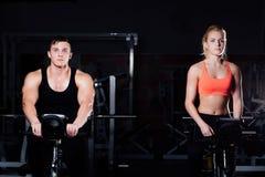 Couples sportifs exerçant à la forme physique le vélo d'exercice sur un gymnase foncé Photo libre de droits
