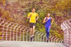 Couples sportifs pulsant au parc en été Images libres de droits