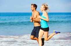 Couples sportifs pulsant ensemble sur la plage Photo stock
