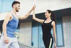 Couples sportifs se donnant la haute cinq Photo stock