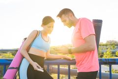 Couples sportifs se reposant apr?s l'exercice utilisant le t?l?phone portable photos stock