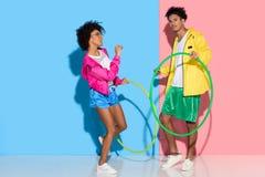 Couples sportifs se tenant avec des cercles sur le rose et le bleu image stock