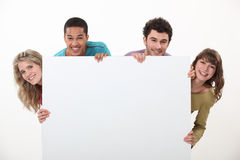 Couples stood with advertising board Stock Photo