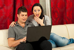 Couples stupéfaits à la maison utilisant l'ordinateur portatif Photo stock