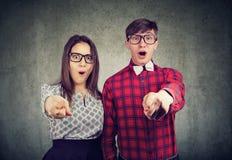 Couples stupéfaits regardant étonnés l'appareil-photo dirigeant des doigts à vous photos libres de droits