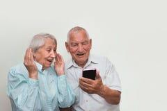 Couples supérieurs à la maison utilisant des smartphones Images stock