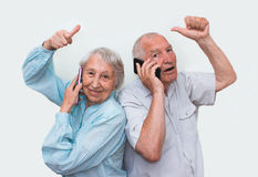 Couples supérieurs à la maison utilisant des smartphones Photo stock