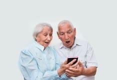 Couples supérieurs à la maison utilisant des smartphones Images libres de droits