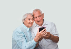Couples supérieurs à la maison utilisant des smartphones Image libre de droits