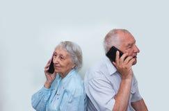 Couples supérieurs à la maison utilisant des smartphones Photo libre de droits
