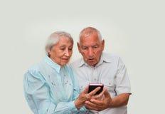 Couples supérieurs à la maison utilisant des smartphones Image stock