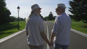 Couples supérieurs élégants marchant tenant des mains banque de vidéos