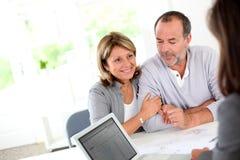 Couples supérieurs achetant la nouvelle maison à l'agence immobilière Photos libres de droits