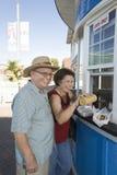 Couples supérieurs achetant le hot-dog au stand de nourriture Photographie stock libre de droits