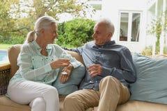 Couples supérieurs actifs ayant le champagne dans le porche photo libre de droits
