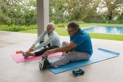 Couples supérieurs actifs faisant étirant l'exercice dans le porche à la maison photos libres de droits