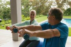 Couples supérieurs actifs s'exerçant avec l'haltère en porche à la maison photographie stock libre de droits