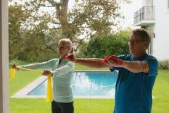 Couples supérieurs actifs s'exerçant avec la bande de résistance en porche à la maison image stock